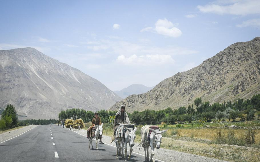 Farmers ride donkeys along a paved road in Afghanistan's Badakhshan province on July 14, 2019, bringing goods into Baharak, a district center under Taliban threat.