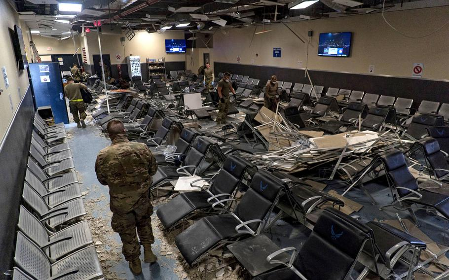 U.S. Air Force airmen from the 405th Expeditionary Support Squadron work together to clear debris inside the passenger terminal the day after a Taliban attack at Bagram Airfield, Afghanistan, Dec. 12, 2019.