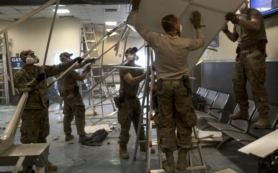 U.S. Air Force airmen from the 405th Expeditionary Support Squadron remove damaged metal and ceiling tiles inside the passenger terminal the day after a Taliban attack on Bagram Airfield, Afghanistan, Dec. 12, 2019.