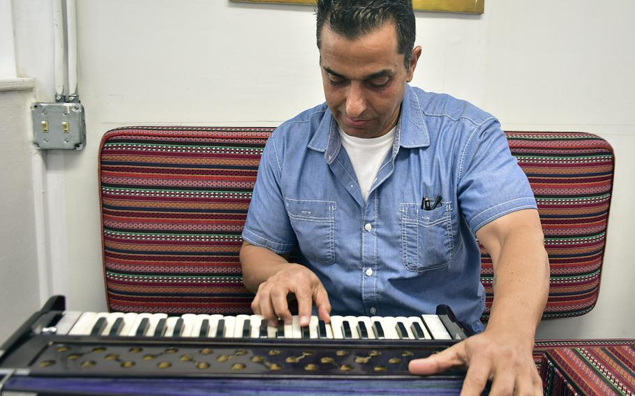 Jawid Kaderi, an Afghan-American contractor who works at Bagram Airfield, plays a traditional Afghan instrument, the harmonium, Sept. 19, 2019. Kaderi each week plays Afghan music to share his culture and history with troops on base.