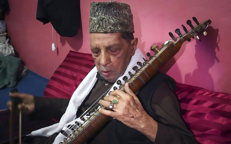 Ustad Amruddin plays a traditional Afghan instrument, the dilruba, at his home in the musician's quarter of Kabul, Afghanistan. Amruddin, 88, lived through the flourishing of music and the arts in Afghanistan in the 1950s, the banning of music under the Taliban and the return of musicians to the country after 2001.