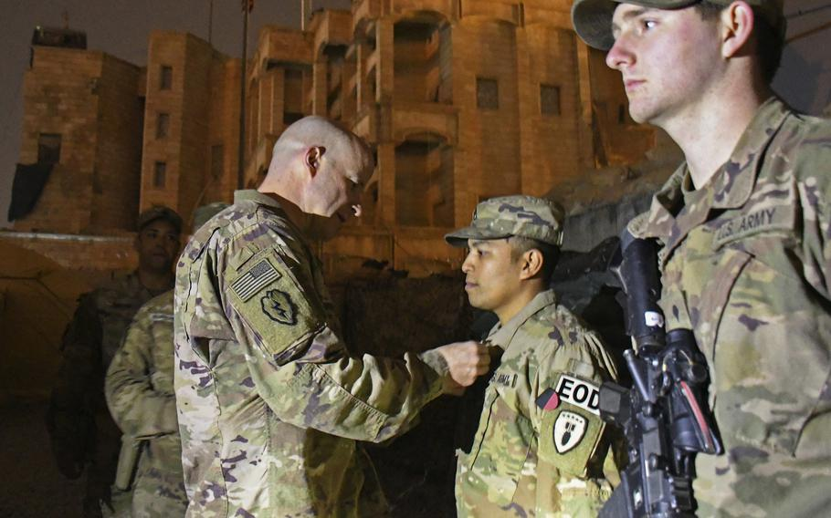 Col. Matthew W. Brown, commander of the 1st Stryker Brigade Combat Team, 25th Infantry Division, pins medals on Staff Sgt. Anthony Lee, left, and Spc. Logan Matthews during a ceremony at a camp in Mosul, Iraq, on Thursday, Dec. 26, 2019.