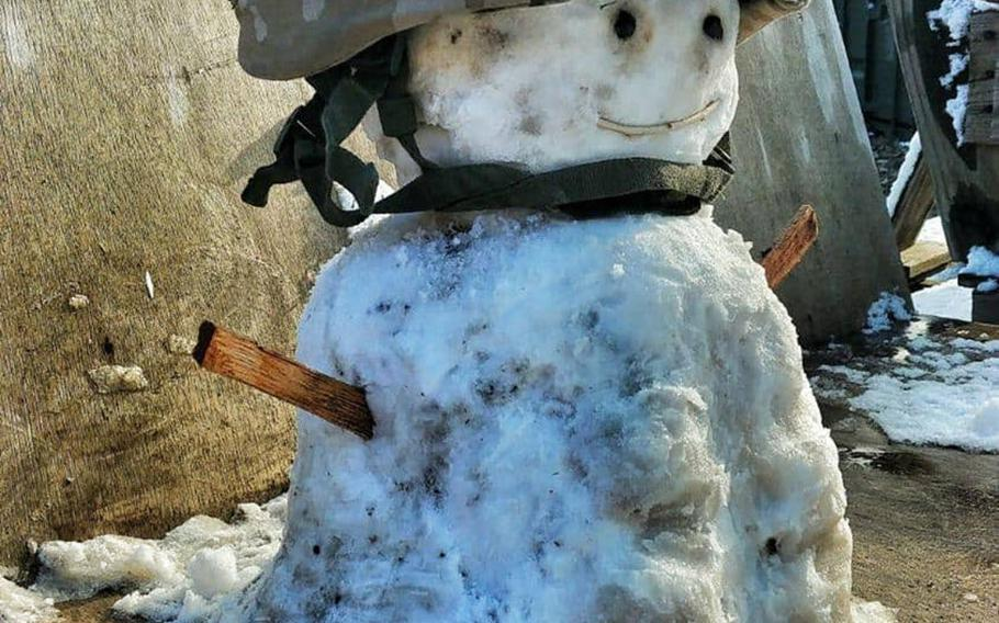 A small snowman sporting a military helmet was built at Camp Taji, Iraq, by Spanish soldier Cpl. David Miranda after a rare snowfall in Baghdad on Tuesday, Feb. 11, 2020.