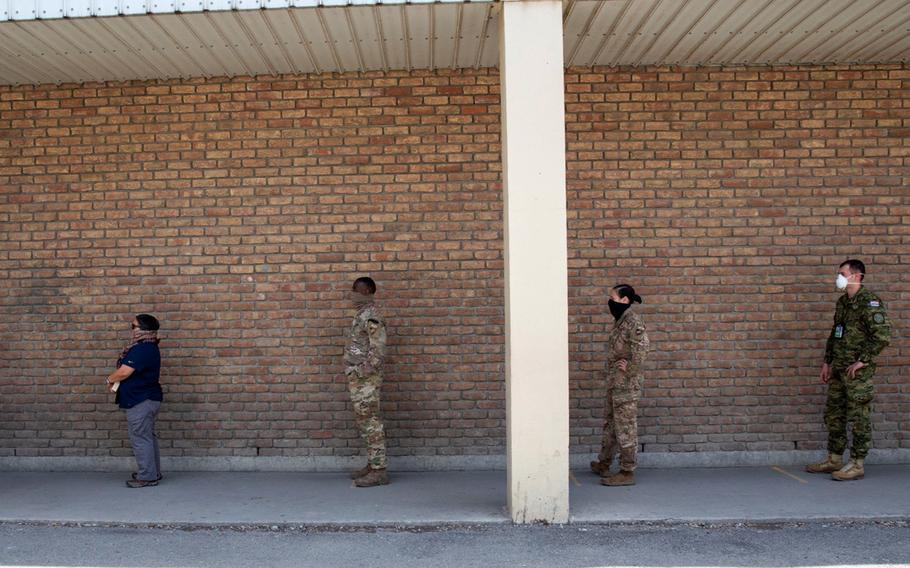 NATO Resolute Support service members and civilians wait for lunch at a dining facility in Kabul, Afghanistan, April 10, 2020. Personnel at RS must wear face coverings and stay six feet apart while waiting in line to receive a to-go meal as part of COVID-19 prevention measures.