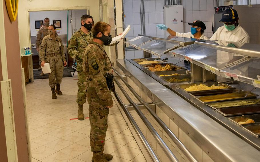 NATO Resolute Support service members and civilians wait for lunch at a dining facility in Kabul, Afghanistan, April 10, 2020. Personnel must wear face coverings and stay six feet apart while waiting in line to receive a to-go meal as part of COVID-19 prevention measures.