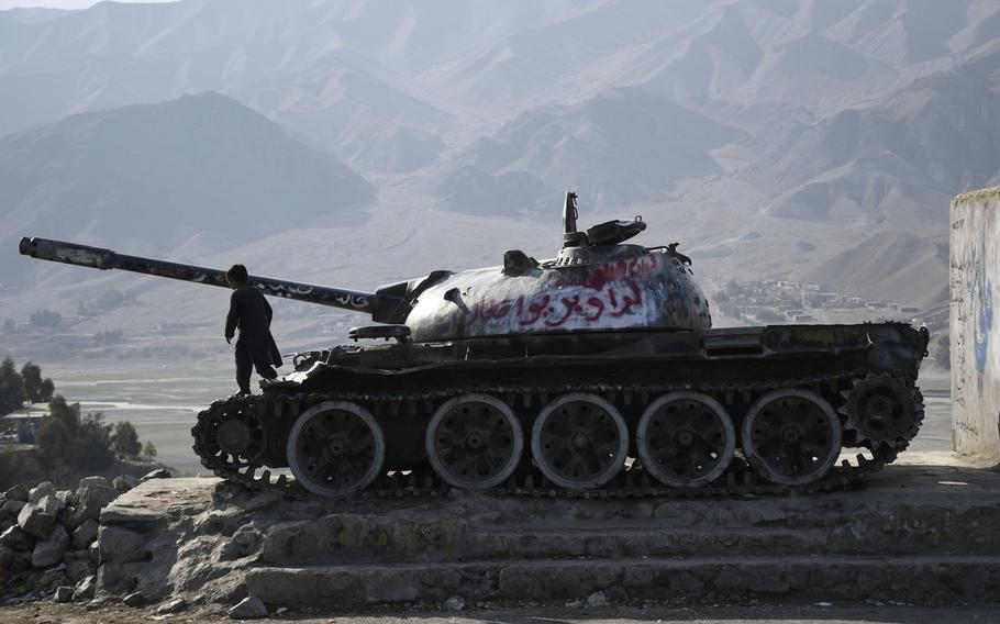 A boy plays on an abandoned Soviet tank on a side of a highway east from Kabul, Afghanistan, on Feb. 22, 2020, the first day of a declared period of reduced violence in the country.