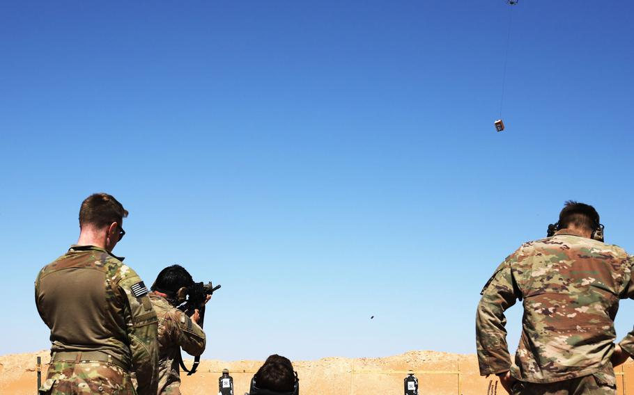 Soldiers take turns using a Smart Shooter sighting device to fire at a box carried by a drone during familiarization range training near al-Tanf garrison, Syria, May 30, 2020.