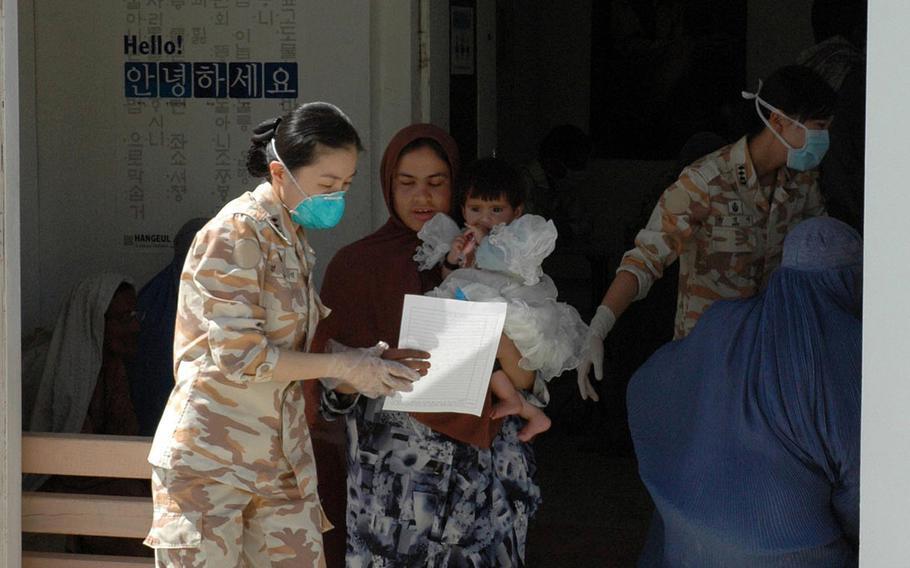 A South Korean army nurse escorts an Afghan woman through a medical wellness check at the Korean Hospital near Bagram Airfield, Afghanistan, in a photo taken April 25, 2007. The hospital was heavily damaged in a Taliban attack on Dec. 11, 2019, and now is being razed, NATO Resolute Support officials said this week.