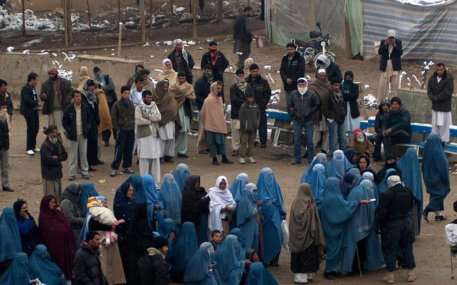 Afghans wait in line to be seen at the South Korean hospital at Bagram Airfield, in a photo taken Feb. 28, 2011. The hospital, largely unused since 2016, was heavily damaged in a Taliban attack on Dec. 11, 2019, and now is being razed, NATO Resolute Support officials said this week.
