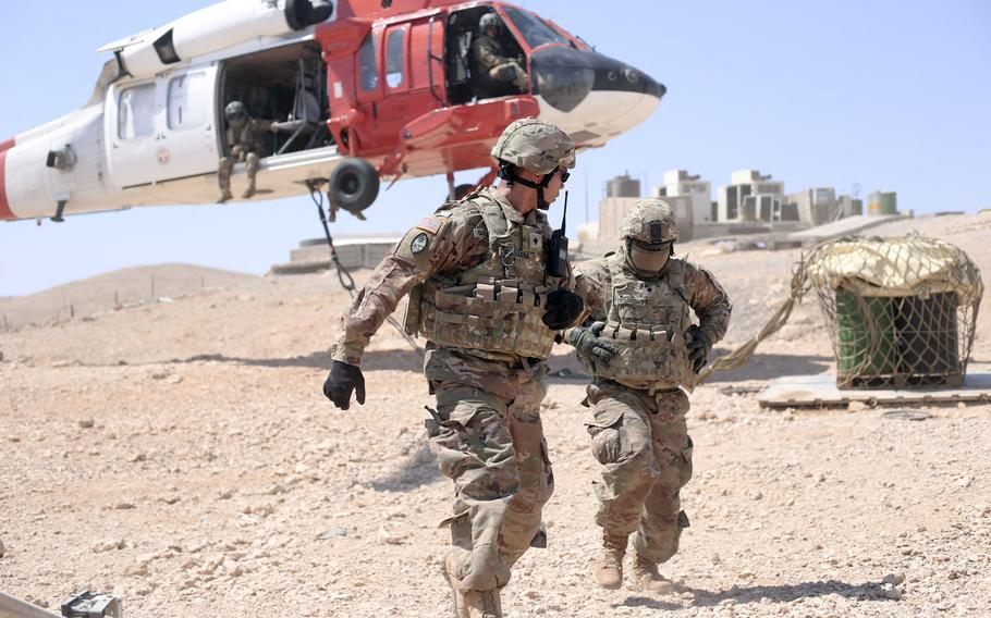 Spc. Richard Guevarra, left, and Spc. Christopher Crisostomo, of the Guam Army National Guard, return from hooking a slingload to a Task Force Sinai Aviation Company UH-60 Blackhawk, at a Multinational Force and Observers remote site in Saudi Arabia in September 2019. The Army has authorized soldiers who have served in Saudi Arabia  since September 2019 to wear combat patches.