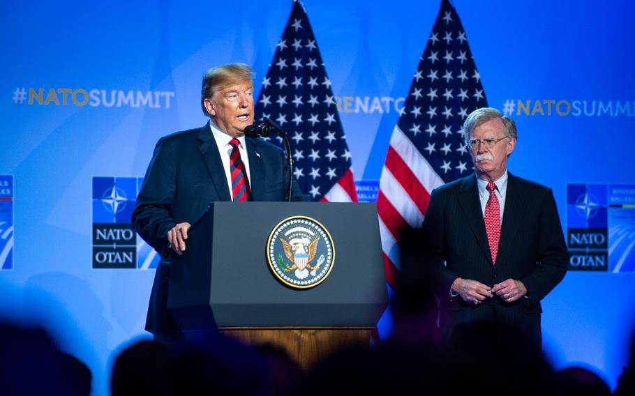 President Donald Trump and National Security Adviser John Bolton give a press conference at the NATO summit in Brussels in July 2018. Bolton recounted Trump's decisions on the war in Afghanistan in a book released Tuesday.