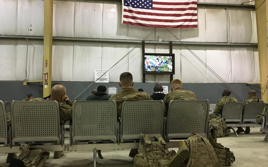 U.S. troops waiting for transport watch the Super Bowl at Bagram Air Field's rotary PAX terminal on Monday, Feb. 4, 2019. A bipartisan group of U.S. lawmakers has introduced a bill that would require Congress to oversee further drawdowns of American troops from Afghanistan.