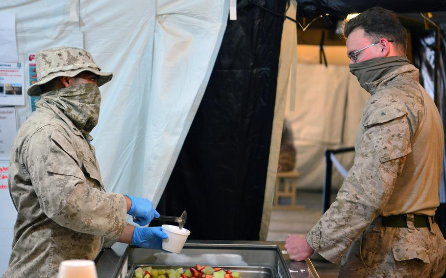 A U.S. Marine Corps volunteer prepares a meal for a fellow Marine at the Sandstorm field kitchen, Ahmed al-Jaber Air Base, Kuwait, April 17, 2020. The Sandstorm was stood up in an effort to further adhere to health protection levels by providing an additional avenue for customers to have a meal. A ''cluster'' of COVID-19 cases has developed at the base, officials said.