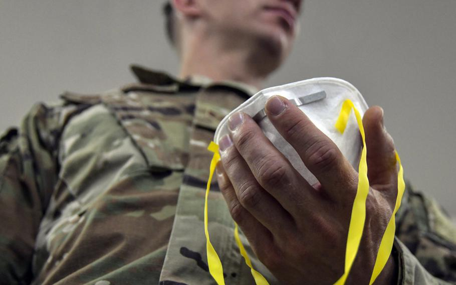 An airman assigned to 407th Expeditionary Logistics Readiness Flight adjusts the straps of his N95 mask to begin a fit test at Ahmed al-Jaber Air Base, Kuwait, March 13, 2020. A ''cluster'' of COVID-19 cases has developed at the base, officials said.