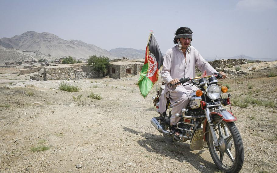 Hekmatullah, 20, a militia fighter in Achin district in eastern Afghanistan drives to his post on July 26, 2020. Hekmatullah stands guard at the same outpost where his father died fighting the Islamic State.
