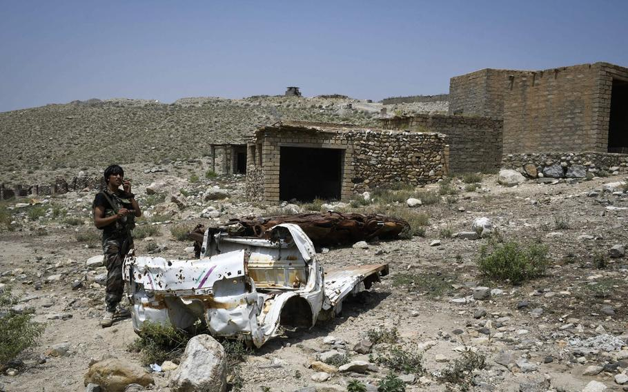 An Afghan militia fighter walks past two cars destroyed in an airstrike by the U.S. against Islamic State positions in the Achin district of Nangarhar provinc, Afghanistan on July 26, 2020. The surrounding market was also destroyed in the battle, locals said.