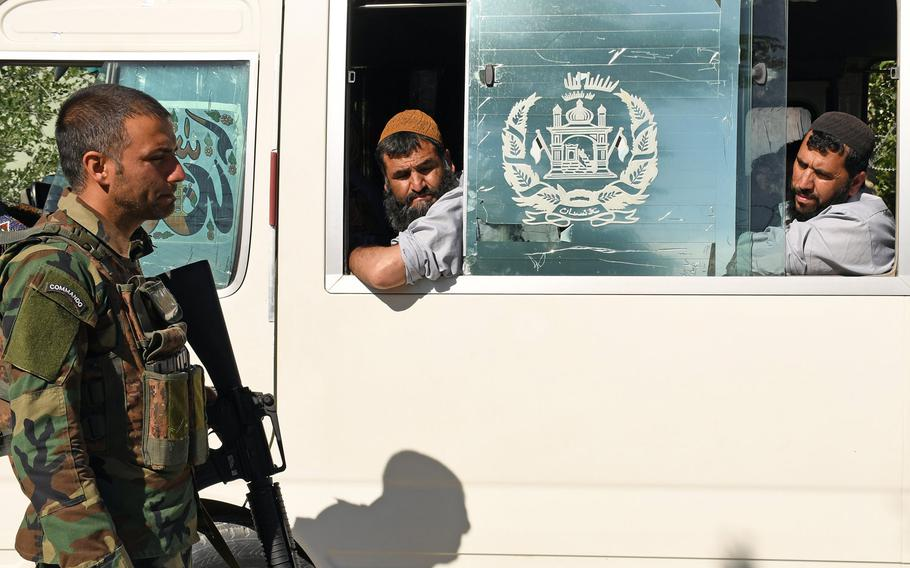 An Afghan soldier exchanges a glance with a Taliban prisoner being released from government custody in May. While violence has spiked across the country in recent months, on Friday the Taliban and government forces announced a three-day cease-fire to mark the Islamic holiday of Eid al-Adha.