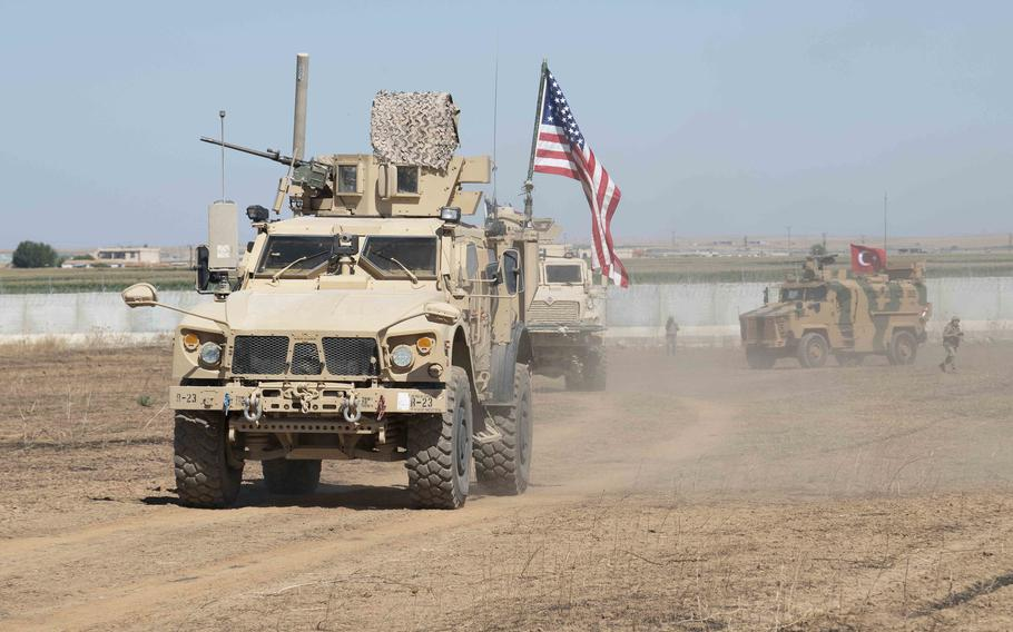 In a September, 2019 photo, U.S. and Turkish military forces conduct a joint ground patrol in northeast Syria. U.S.-led coalition and partner forces returned fire after an attack on their convoy near a Syrian military checkpoint Monday, Aug. 17, 2020, a coalition statement said.