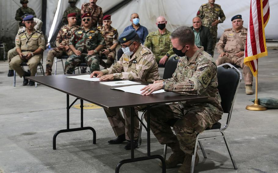 Iraqi Brig. Gen. Salah Muhammed Abdullah, and U.S. Air Force Maj. Gen. Kenneth P. Ekman, the deputy commander for operations for Combined Joint Task Force-Operation Inherent Resolve, participate in a signing ceremony to officially transfer Camp Taji to the Iraqi security forces at Camp Taji, Iraq, Aug. 23, 2020.