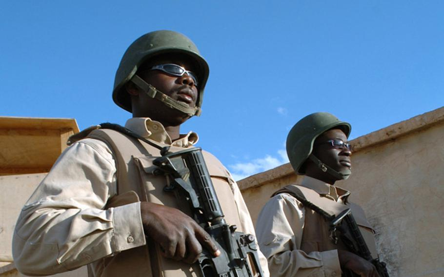 Two Ugandan contractors guard an American base in the Middle East in 2006. Of some 300 Ugandan guards at Operating Base Fenty near Jalalabad, in eastern Afghanistan, a majority tested positive for the coronavirus in June.