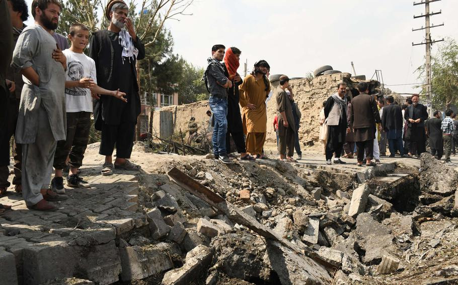 Residents look at the site in Kabul where a blast gouged a large hole in the street and destroyed several buildings on Wednesday, Sept. 9, 2020. The explosion, which killed at least 10 civilians, targeted First Vice President Amrullah Saleh, who was slightly injured.