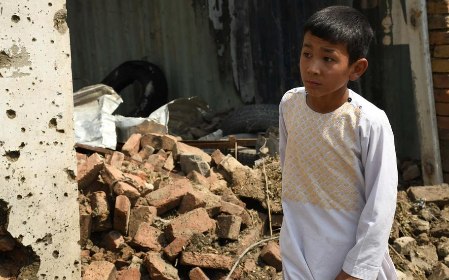 An Afghan boy inspects damage caused by a bomb blast in Kabul on Wednesday, Sept. 9, 2020. First Vice President Amrullah Saleh, who was the target of the attack, was only slightly injured in the blast, which killed at least 10 civilians.