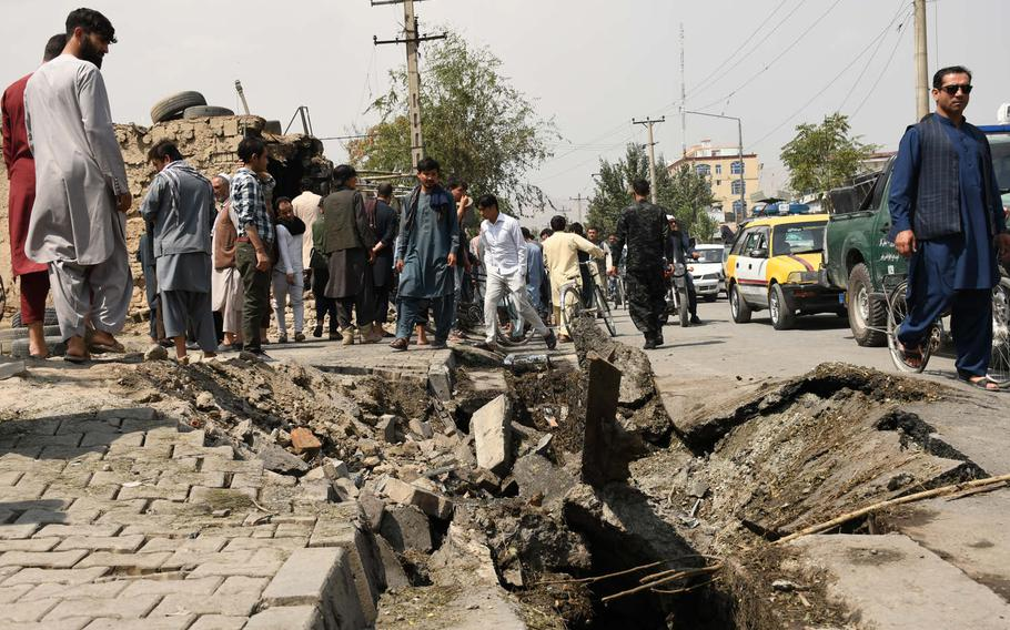 Kabul residents pass by the site where a bomb targeting First Vice President Amrullah Saleh left 10 civilians dead on Sept. 9, 2020, flattened  buildings and carved a crater into the road. Saleh was only slightly injured in the powerful blast, which he said melted the windows of the car he was in.