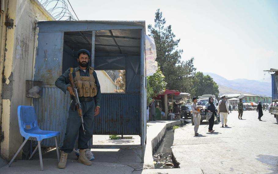 An Afghan policeman guards the entrance of a government building in Faizabad, the provincial capital of Badakhshan province, which was once safe but is now under Taliban threat.