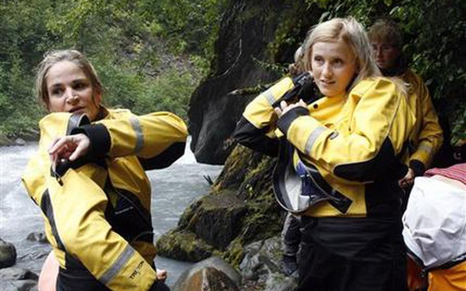 Julie Robinson of Ligonier, Pa., left, and Jennifer Hankins of San Diego, put on wet suits before a white water rafting trip on Crow Creek, near Girdwood, Alaska in early August 2011.