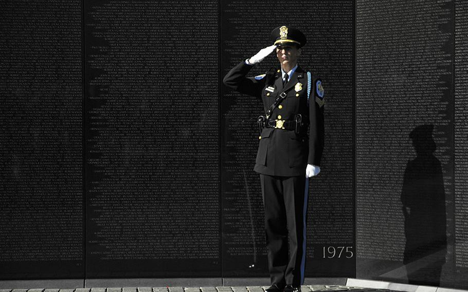 A police officer salutes during a wreath-laying ceremony at the Vietnam Veterans Memorial wall on Veterans Day, Nov. 11, 2012.