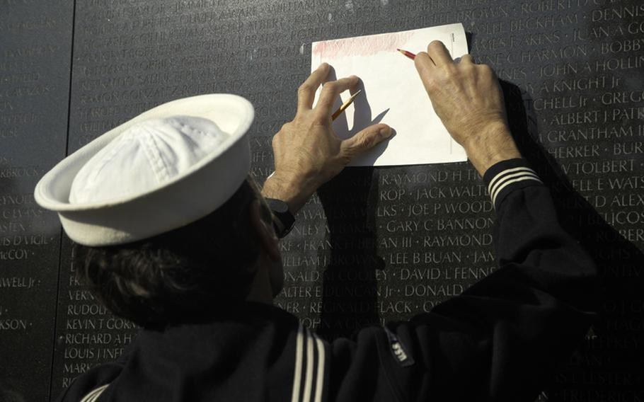 A visitor to the Vietnam Veterans Memorial on Nov. 11, 2012 makes a copy of a name on the wall.