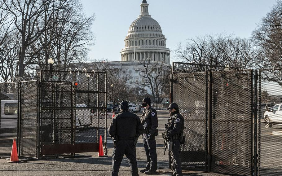 Capitol Police officers stand at an entry point through fencing that surrounds the Capitol complex on March 3, 2021.