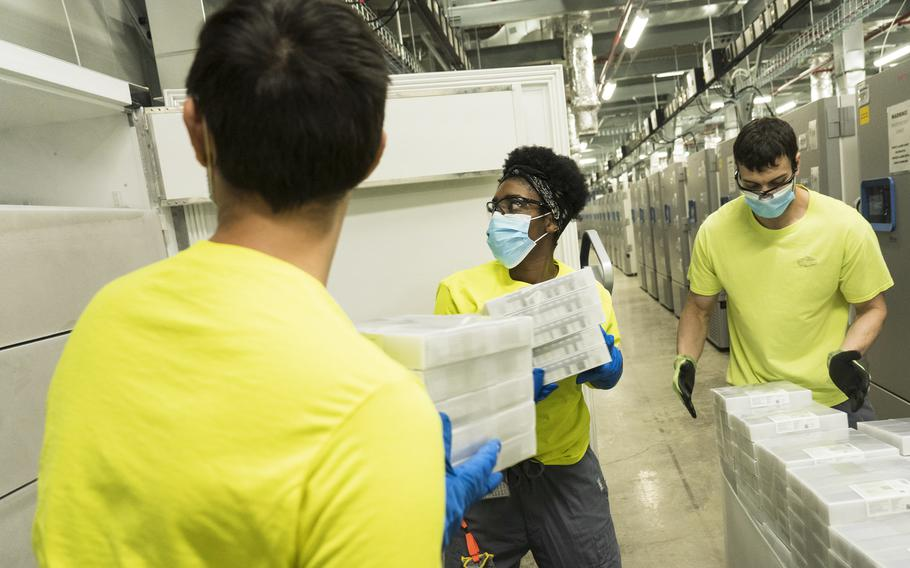 Pfizer freeze operation technicians load vaccine doses into a freezer at the Kalamazoo, Mich., facility.