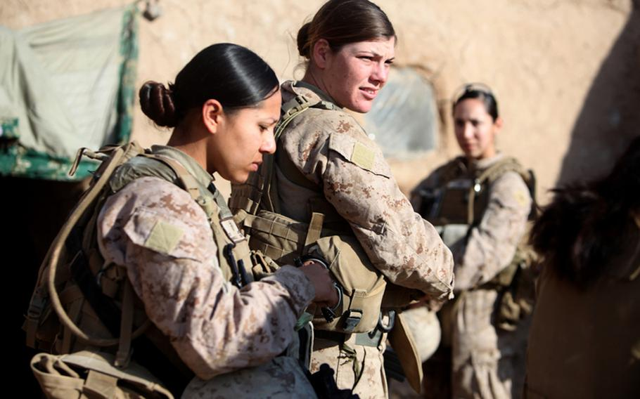 Female Marines assigned to an engagement team speak with a villager in the Helmand province of Afghanistan, Dec. 30, 2010.