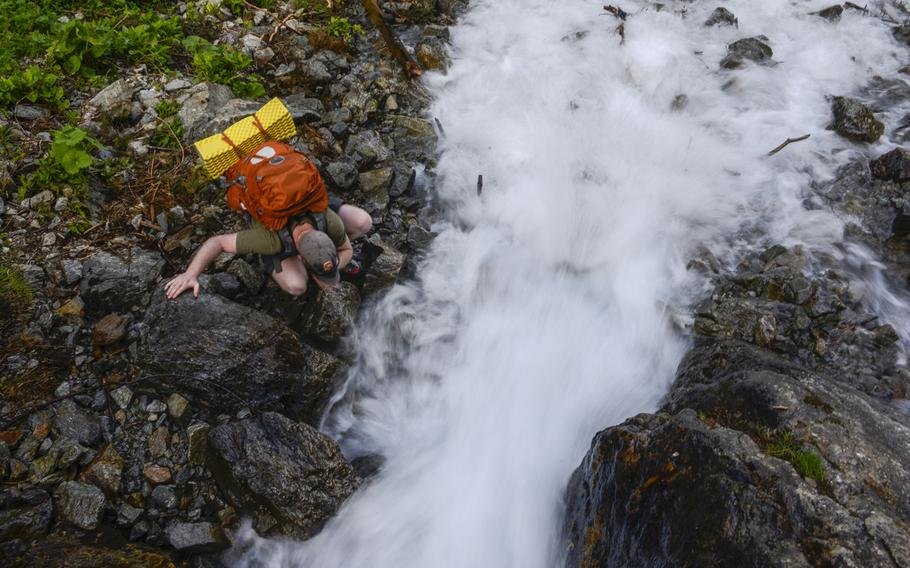 Matt Millham, a Stars and Stripes reporter, drinks from a mountain stream during an overnight hiking trip in Chamonix, France.