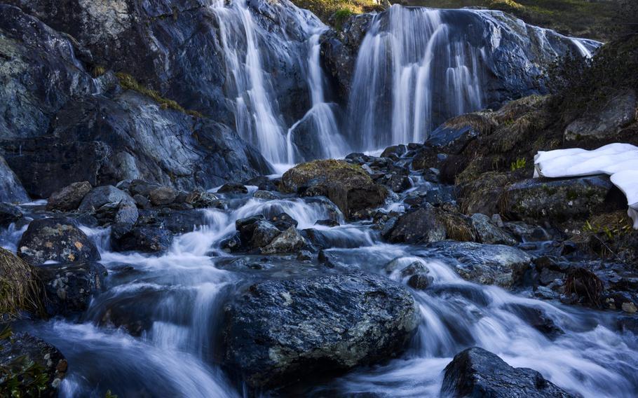 A mountain stream cascades above the Chamonix Valley, France.