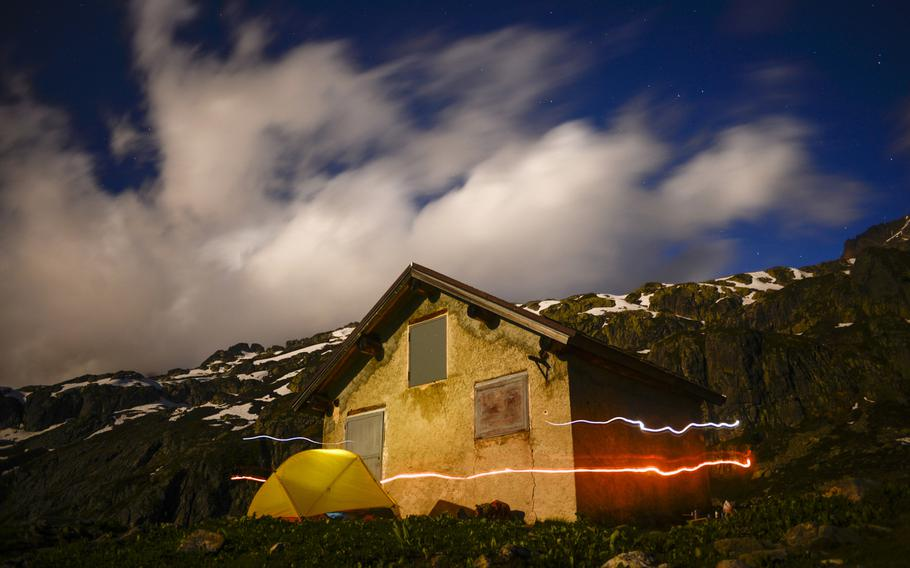Matt Millham's, a Stars and Stripes reporter, headlight and lamp streak by a camping site in front of the Chalet des Cheserys along a piece of the Tour du Mont Blanc hiking trail above the Chamonix Valley, France.