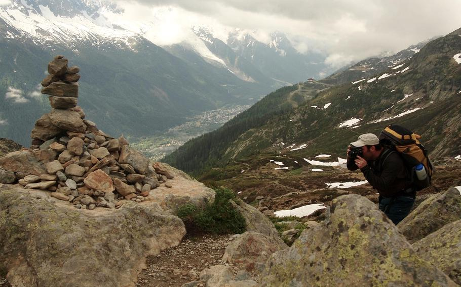 Joshua L. DeMotts, a Stars and Stripes photographer, photographs a man-made pile of rocks known as cairns along the Tour du Mont Blanc during an overnight hiking trip above the Chamonix Valley, France.