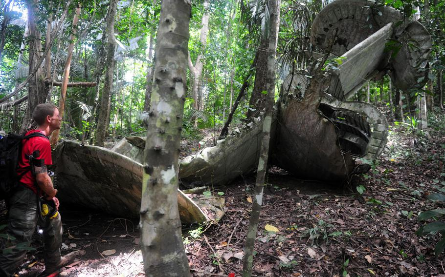 A member of a a JPAC recovery team observes wreckage from a B-24 Liberator during excavation operations in Madang Province in Papua New Guinea in this 2008 photo.