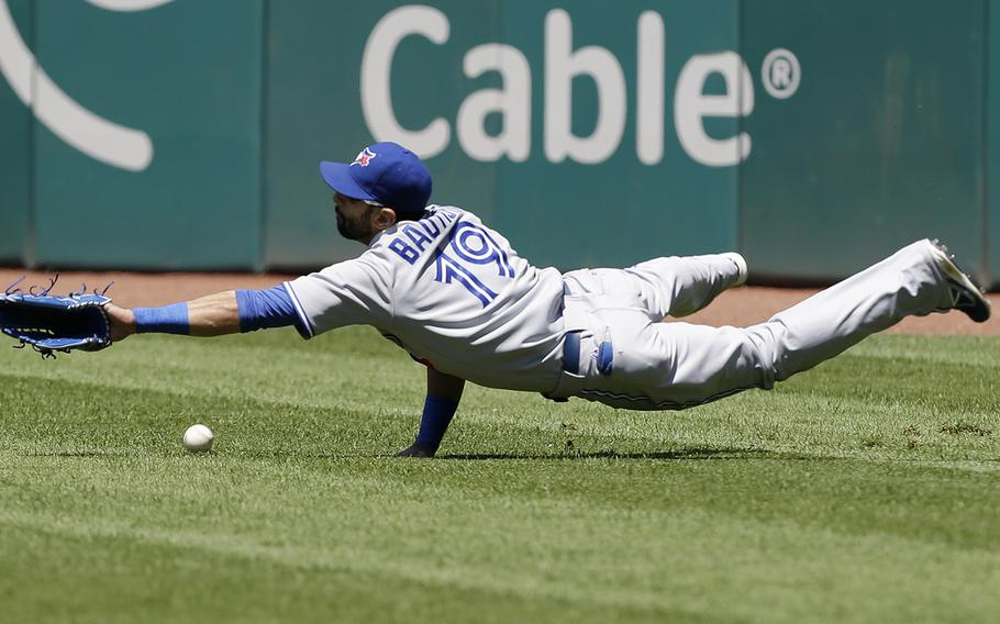 Toronto Blue Jays right fielder Jose Bautista dives for an rbi triple hit by Cleveland Indians' Carlos Santana in the eighth inning of a baseball game, Thursday, July 11, 2013, in Cleveland. The Indians won 4-2. (AP Photo/Tony Dejak)