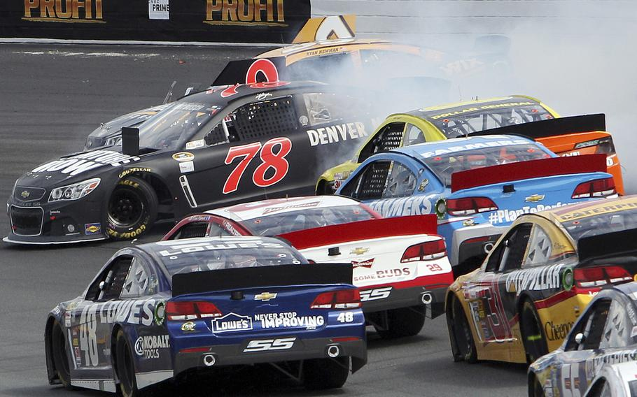 Kurt Busch and Ryan Newman, rear, get sideways in Turn 2 during the NASCAR Sprint Cup series auto race at New Hampshire Motor Speedway, Sunday, July 14, 2013, in Loudon, N.H.  (AP Photo/Jim Cole)