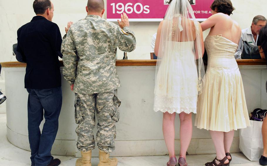 Army Sgt. Michael Potoczniak and his partner, Todd Saunders, left, and Cynthia Wides, left, and Elizabeth Carey go through the process of getting married at City Hall in San Francisco, California,  June 29, 2013.