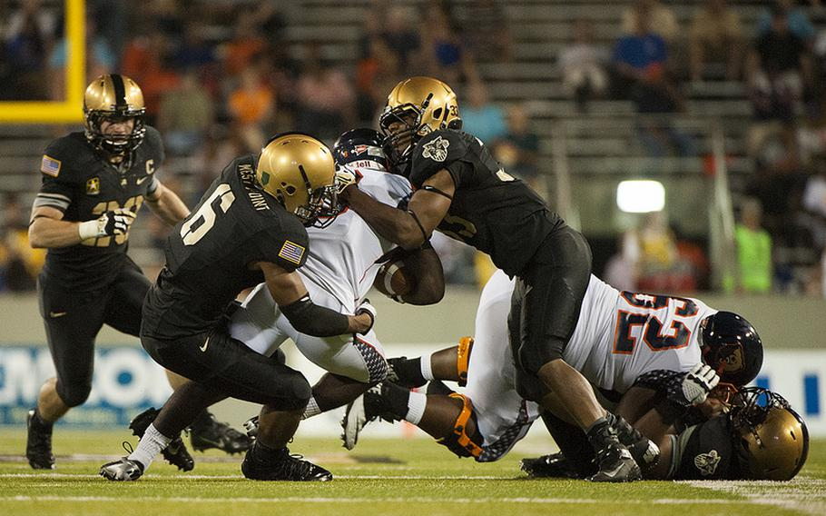 Two Army defenders team up for a tackle during their 28-12 victory over visiting Morgan State Aug. 30, 2013, at Michie Stadium.