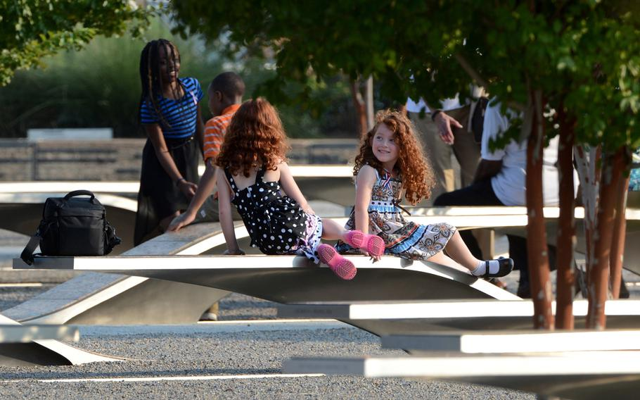 Children rest on the benches of the Pentagon Memorial at the Pentagon in Arlington, Virginia, Wednesday, September 11, 2013. There are 184 benches in the Pentagon Memorial representing the 184 people who died at the Pentagon on September 11, 2001.