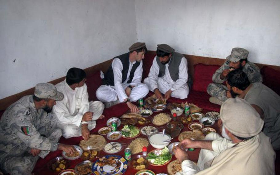 Capt. William Swenson has lunch with Afghan National Army local leadership and former Mujahadeen outside of Asadabad, Afghanistan, in March 2009.