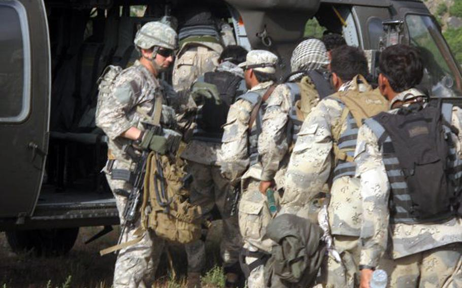 Capt. William Swenson leads Afghan Border Police members as they board a UH-60 Black Hawk helicopter in May 2009.