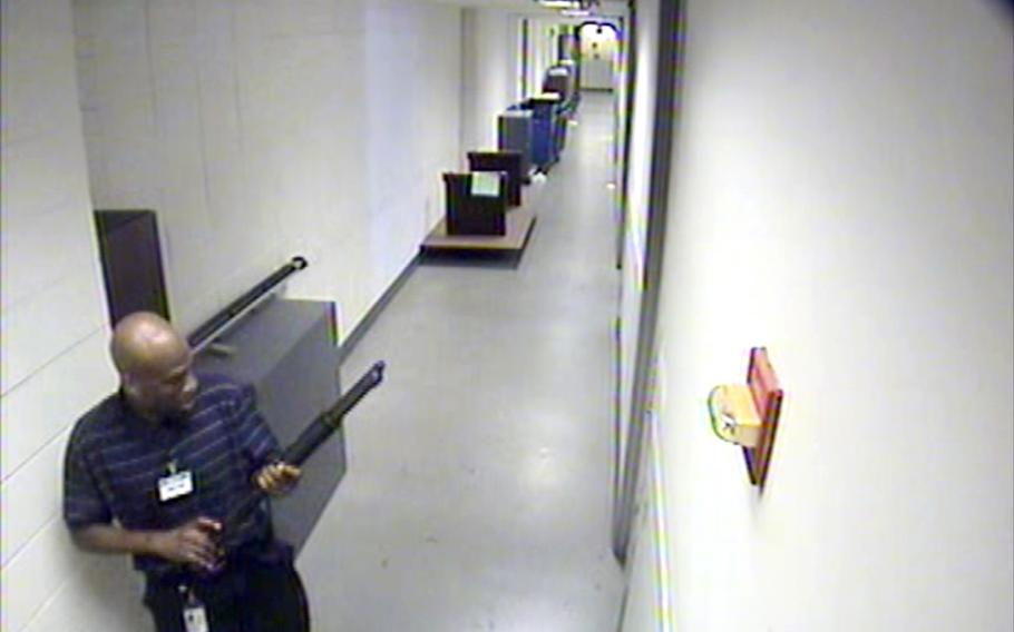 This image from video provided by the FBI, shows Aaron Alexis moves through the hallways of Building #197 at the Washington Navy Yard on Monday, Sept. 16, 2013, in Washington, carrying a Remington 870 shotgun. Alexis, a 34-year-old former Navy reservist and IT contractor, shot and killed 12 people inside a Navy Yard building last week before being killed in a shootout with police.