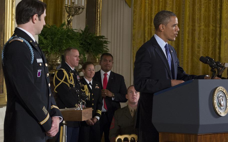 Capt. William Swenson listens as President Barack Obama talks about the battle in Afghanistan in which Swenson earned the Medal of Honor.