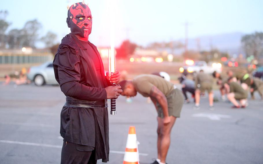 A Marine with Headquarters Company, Combat Logistics Regiment 17, 1st Marine Logistics Group, leads a physical training station during a Halloween-themed PT circuit conducted aboard Camp Pendleton, Calif., Oct. 30, 2013. The Marines wore Halloween costumes and held a festive costume competition at the end of the exercise to build unit cohesion, and provide them an opportunity to unwind and have fun with their peers.