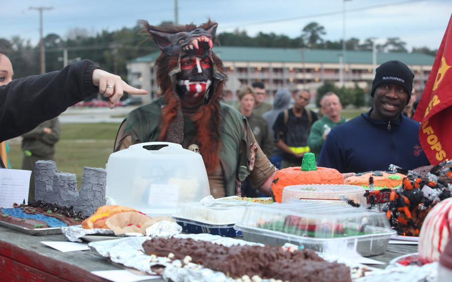 Sgt. Maj. Dennis Downing, Marine Wing Support Squadron (MWSS) 272 sergeant major, auctions off cakes made by each individual company within the squadron as part of the Halloween event conducted by MWSS-272, Oct. 25.